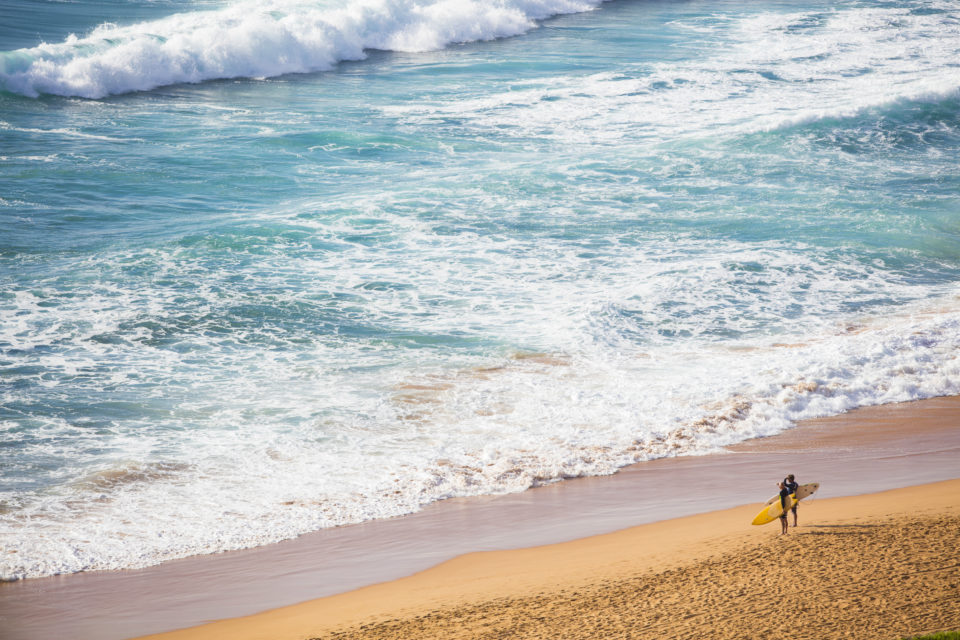 A couple of surfers assess a new swell on the Northern Beaches of Sydney, NSW, Australia.