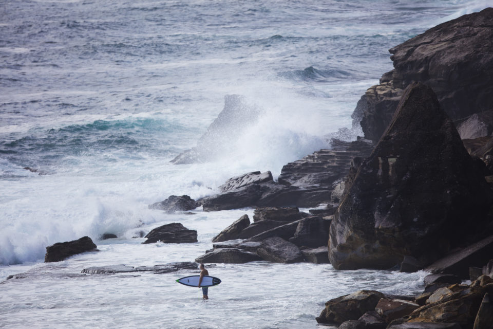 A surfer prepares to negotiate jump rock at LA  on the Northern beaches of Sydney, NSW, Australia.