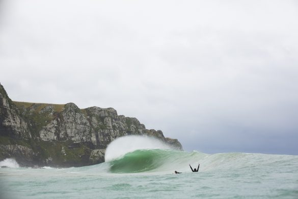 A surfer salutes a peak at a remote beach in the Catlins, New Zealand. Photo: Derek Morrison