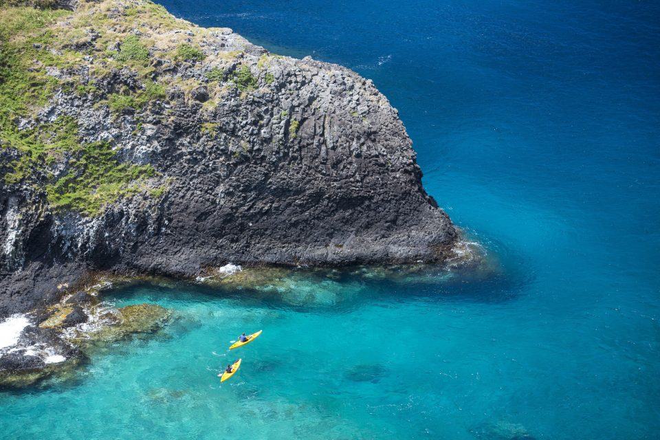 Local surfer Emily Ryves and Dallas Hewett kayak on the sheltered side of the island. Photo: Derek Morrison