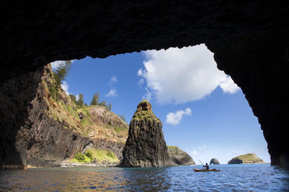 Writer Dallas Hewett kayaks through an archway. Photo: Derek Morrison