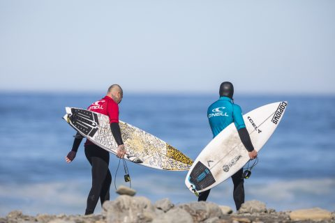 Two big hitters Jai Earnshaw and Levi O'Connor head out for the tag team event during a fun winter swell for the Pete and Danny Memorial Contest. Photo: Derek Morrison