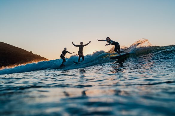 Paige Hareb and friends share a wave on dusk. Photo: RiBLANC